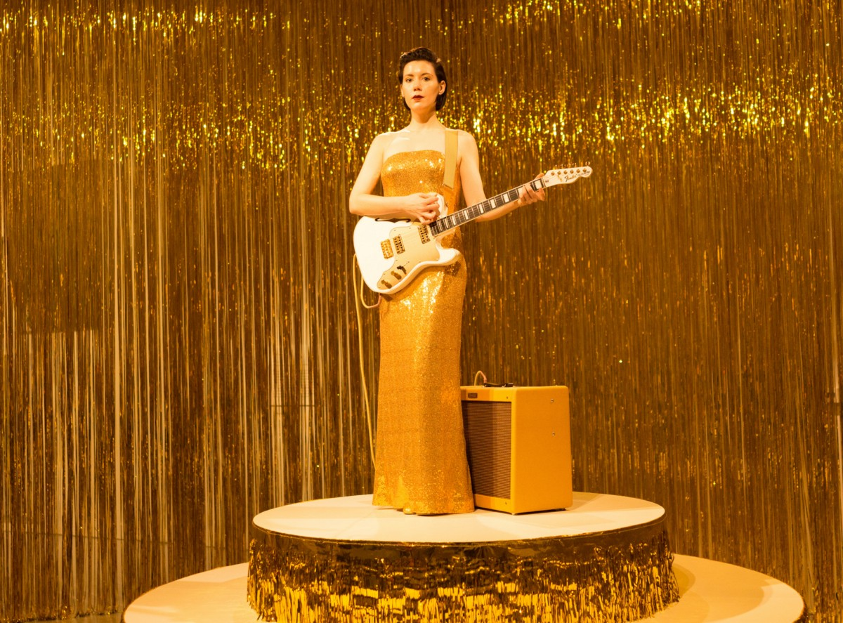 A white woman with dark hair standing on a gold platform, surrounded by gold tinsel, wearing a gold dress, and holding a guitar.