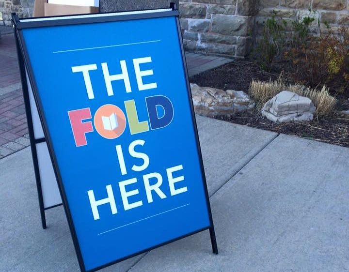 "Sidewalk sign reading ""The FOLD is here,"" advertising the Festival of Literary Diversity"