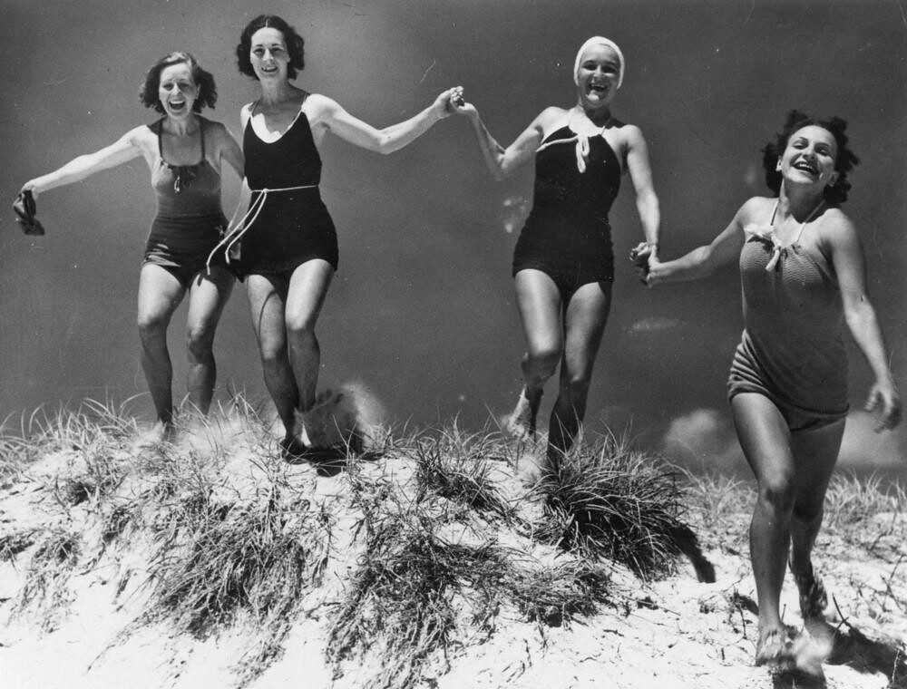 Four friends in 1930s bathing costumes running over a sand dune