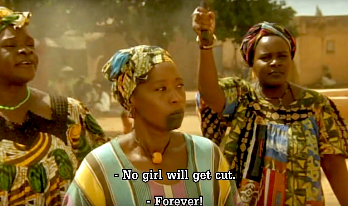 "Three women in traditional African dress stand together. The subtitles read, ""No girl will be cut. Forever!"""