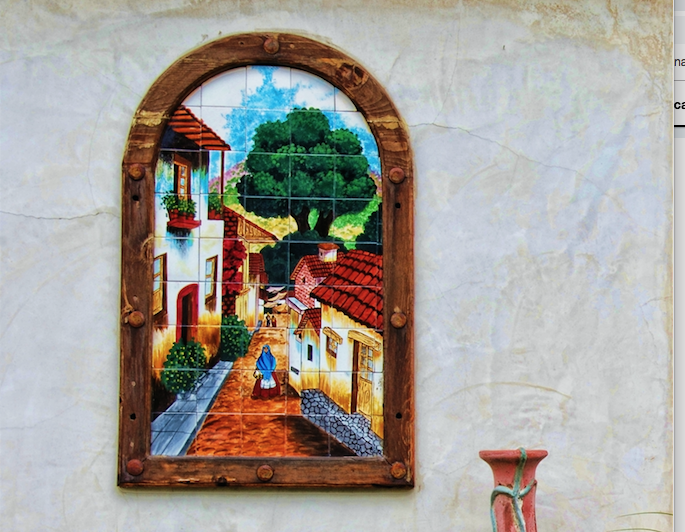 Southwestern-style mosaic showing a street with tiled roofs