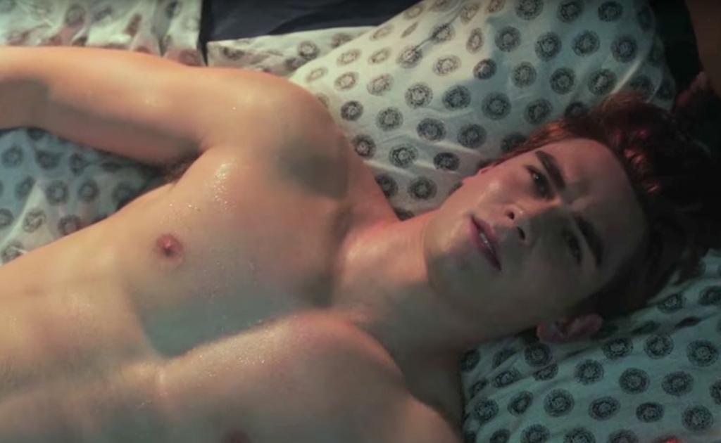 KJ Apa as Archie Andrews, shirtless in bed
