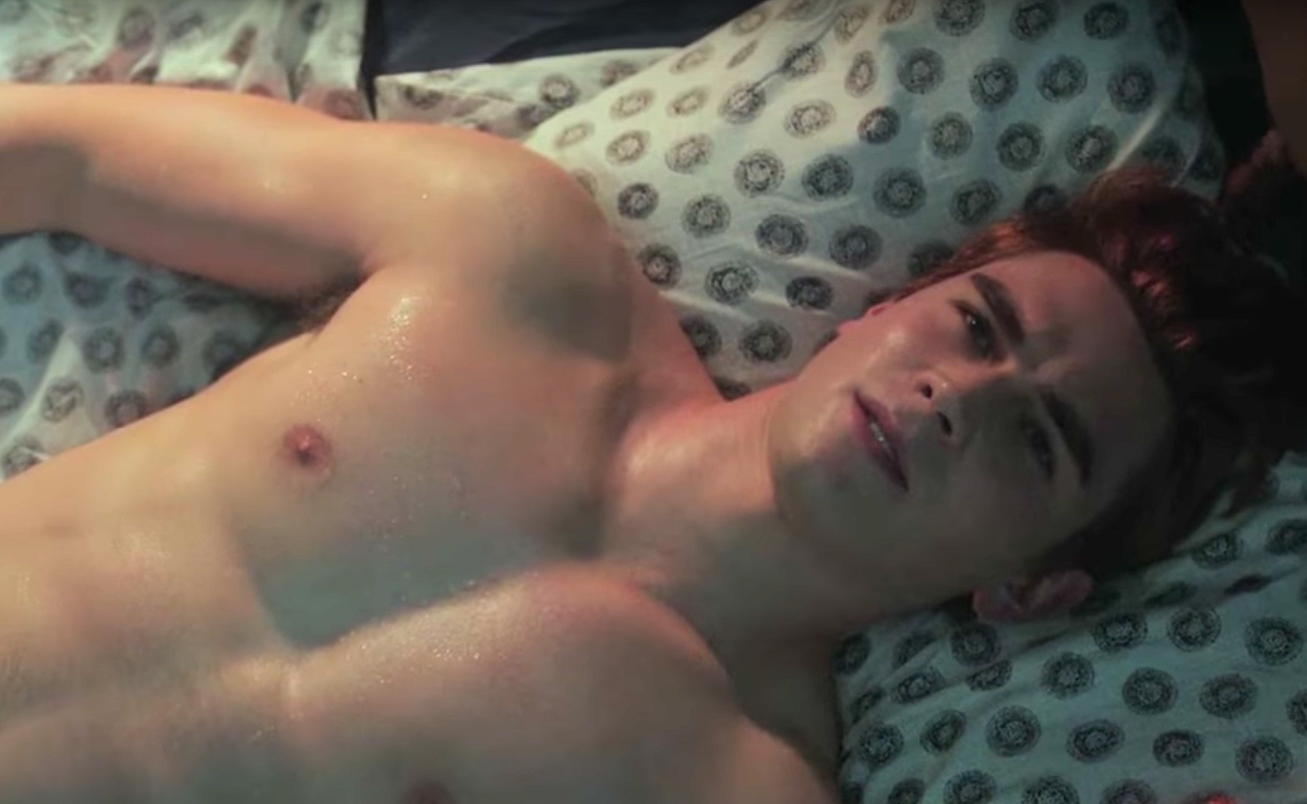 KJ Apa as Archie Andrews, shirtless in bed