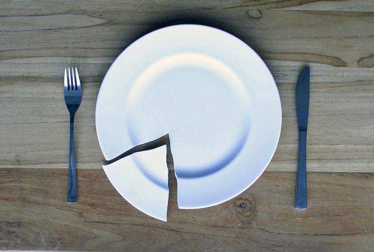 broken white plate with fork and knife