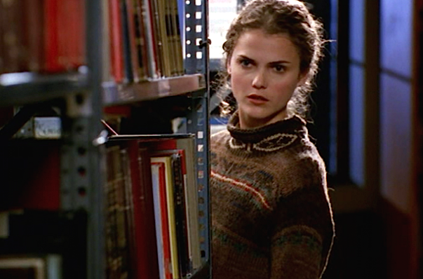 Felicity, played by Keri Russell, looks at a shelf of books in a college library