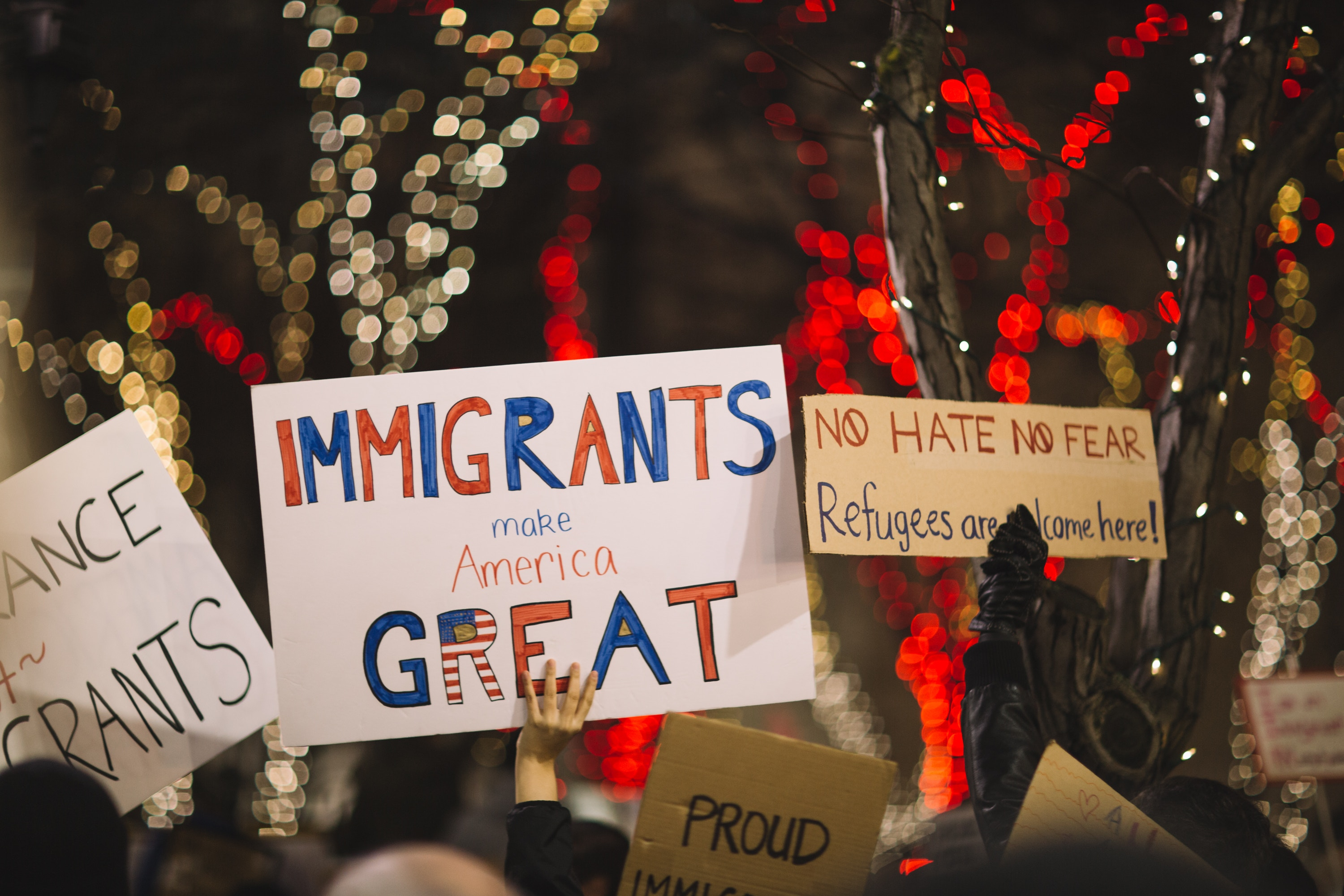 "People at a march holding signs that say ""immigrants make American great"" and ""no hate no fear"""