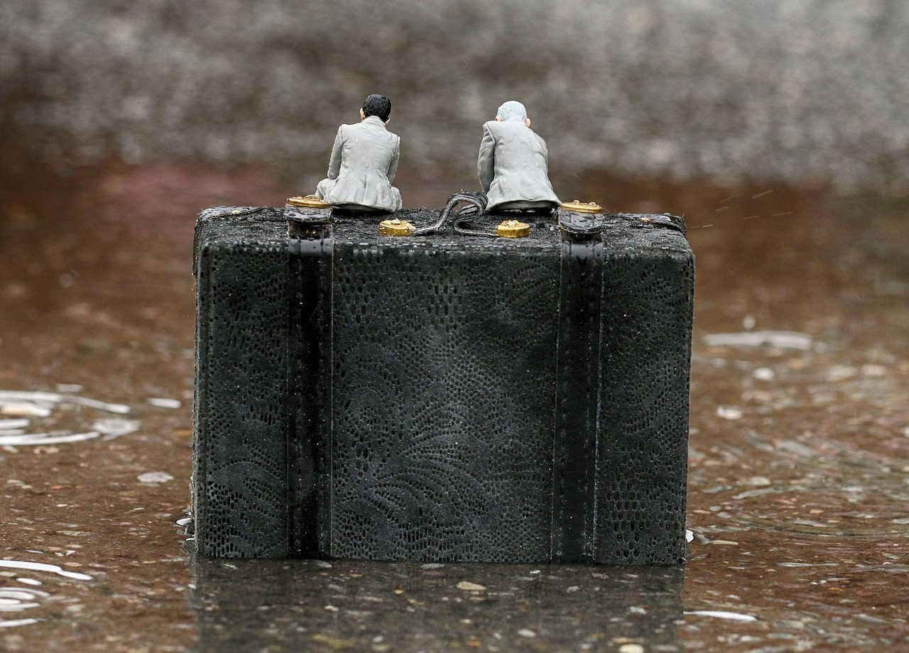 Two miniature figures sitting on a briefcase in the rain
