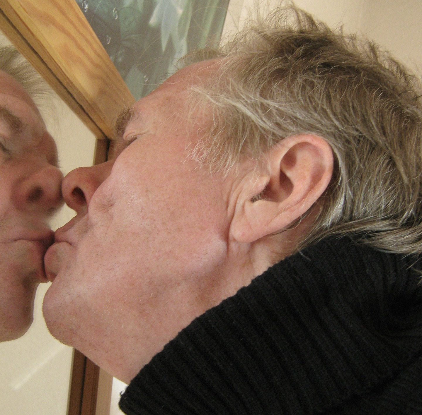 Grey-haired man kissing his reflection in the mirror