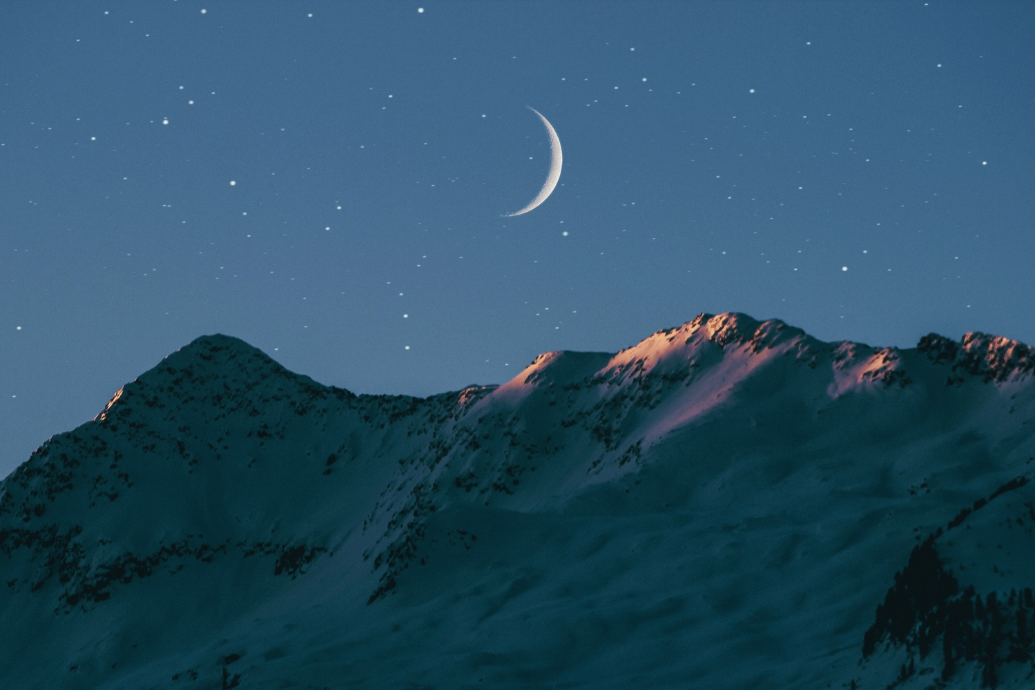 Crescent moon over mountain range