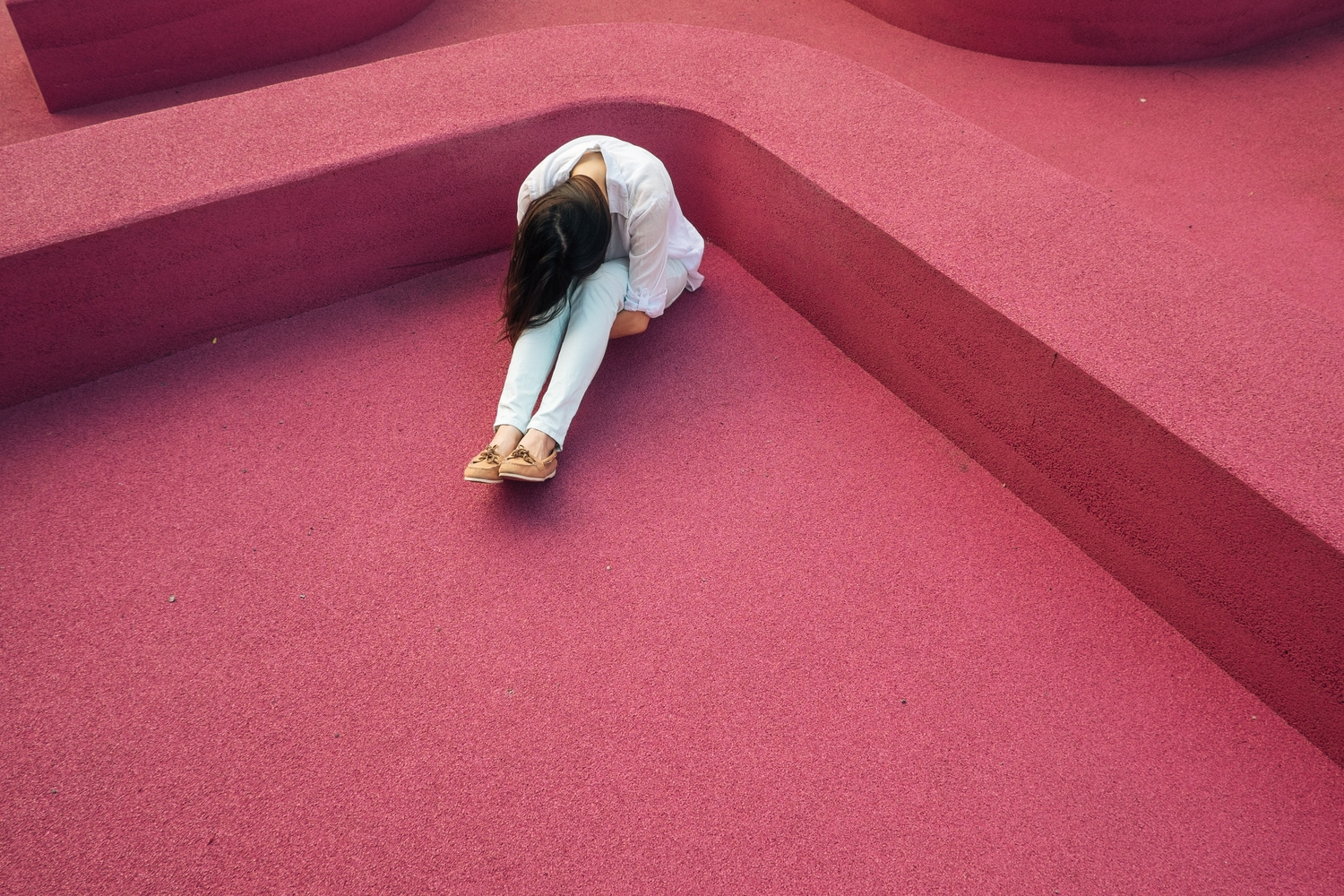 Woman crouched over amidst a pink background