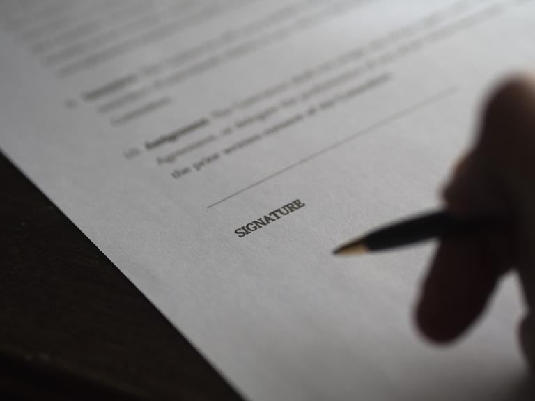 Person hesitating over signature line of contract