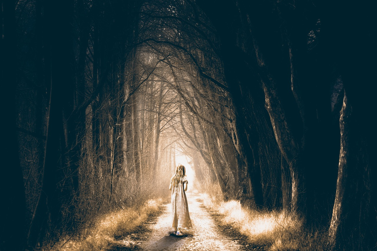 Child in dress walking into spooky forest