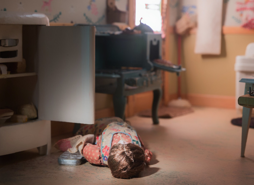 Diorama showing a woman lying on the floor of a kitchen