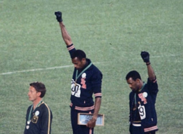 Gold medalist Tommie Smith (center) and bronze medalist John Carlos (right) showing the raised fist on the podium after the 200 m race at the 1968 Summer Olympics; both wear Olympic Project for Human Rights badges.