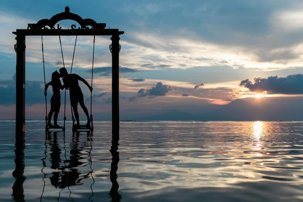 Silhouette of a couple holding hands and kissing while suspended above water