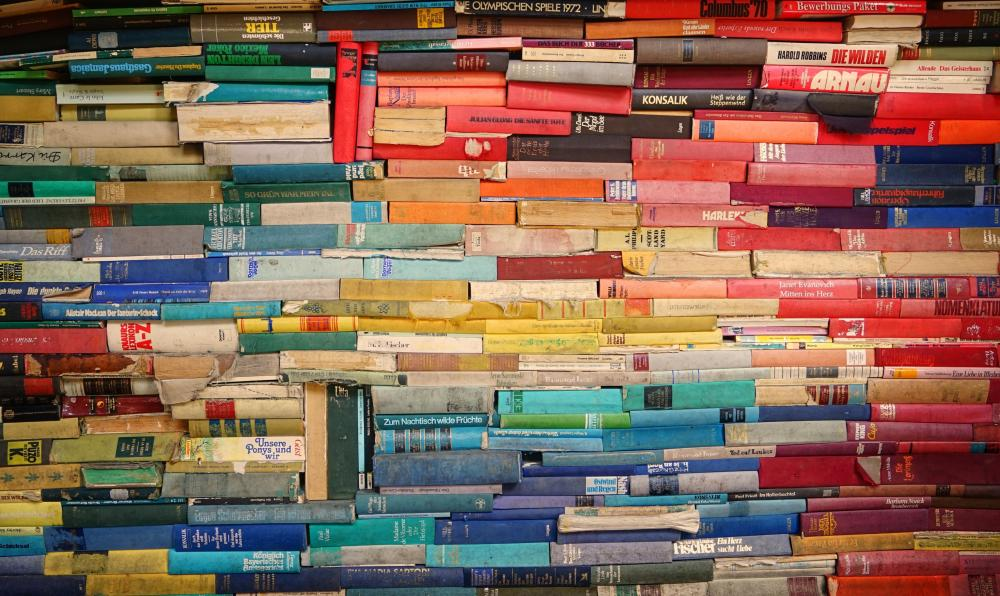 A rainbow of books stacked on their sides, filling the screen
