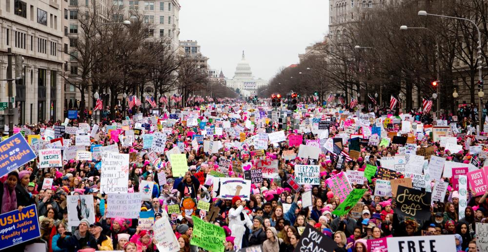 A crowd of women march and protest with the White House in the background