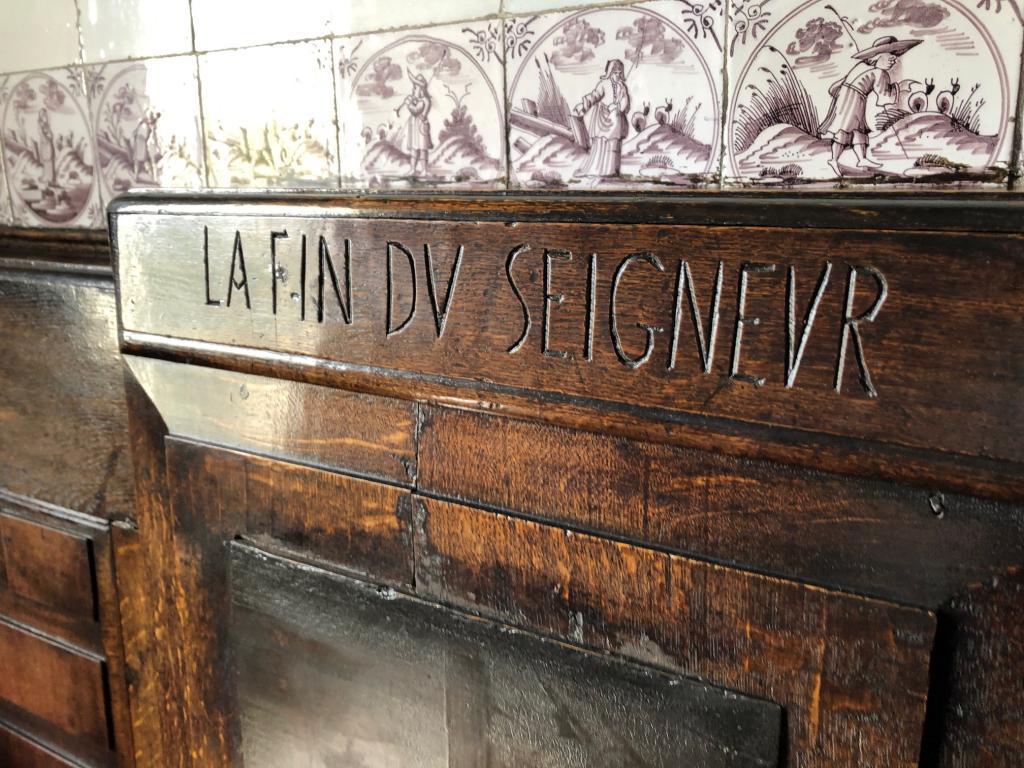 "Inscription incised in wood, reading ""la fin du seigneur."""