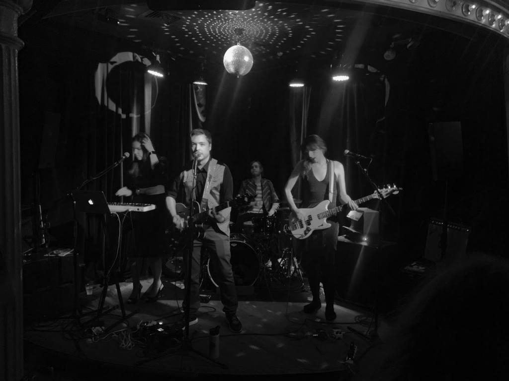 Black and white photo of Dalton Deschain and the Traveling Show performing onstage under a disco ball