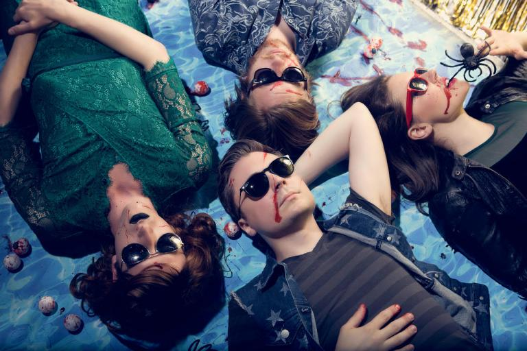 The members of Dalton Deschain and the Traveling Show lying on a picnic blanket covered in fake blood