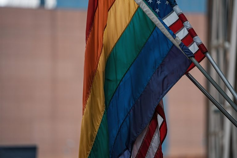 Pride flag and American flags hanging together