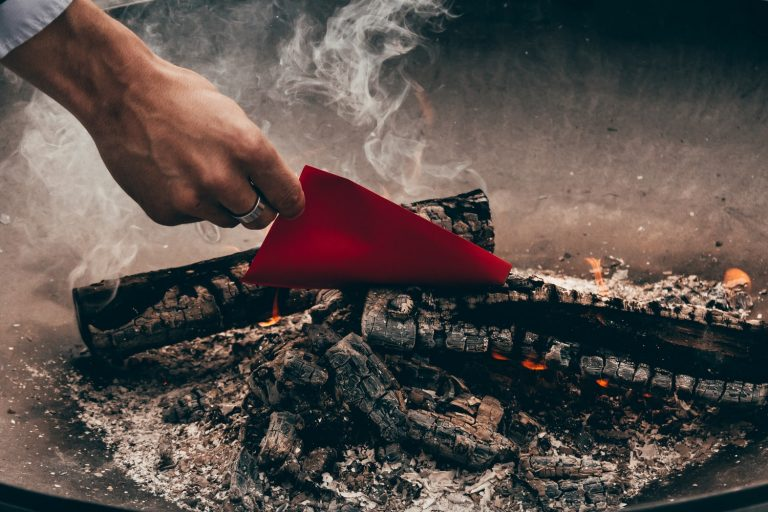 hand putting red paper into fire