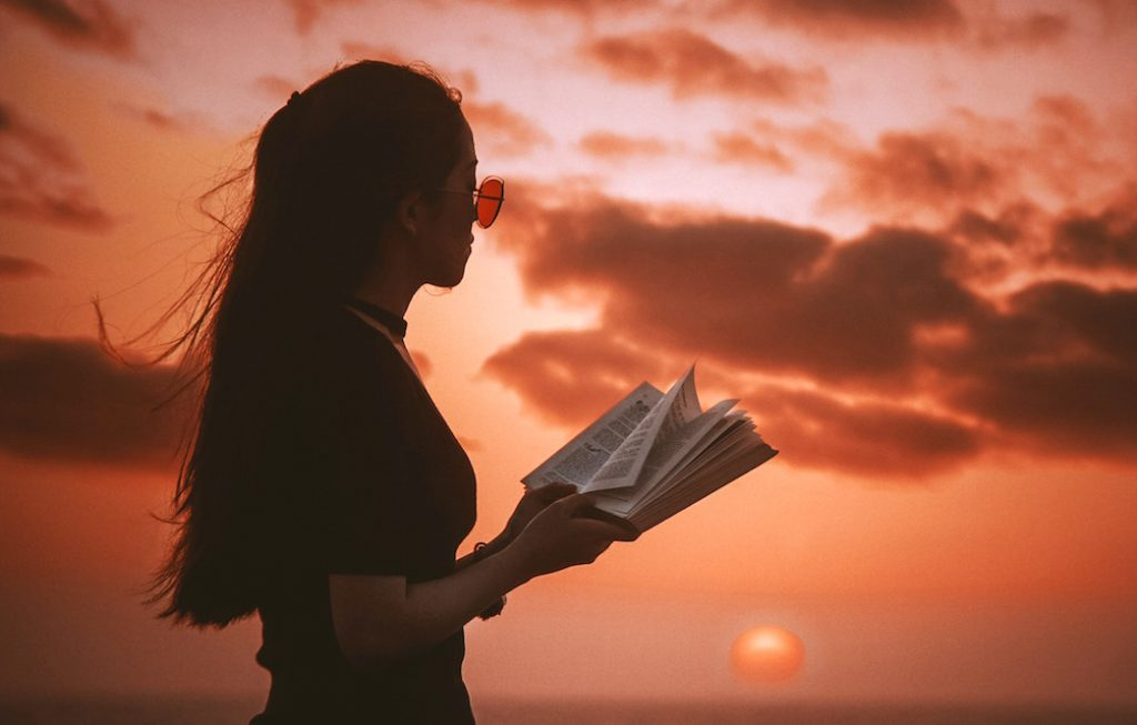 Young woman in sunglasses reading a book at sunset