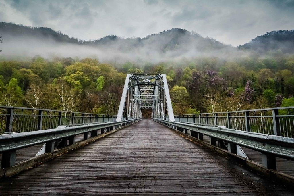 Wooden bridge heading into misty mountains
