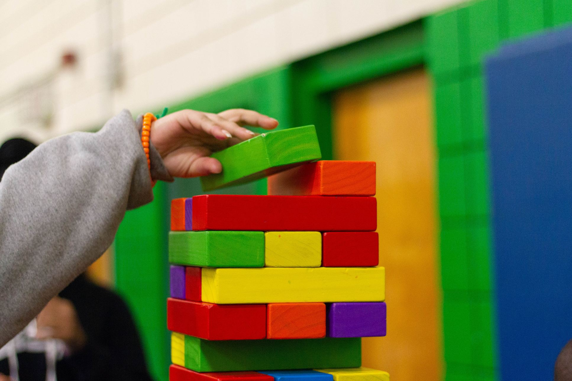 child's hand stacking blocks