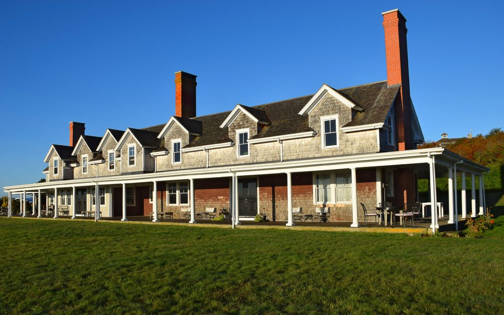 A long building with a wraparound porch and three chimneys