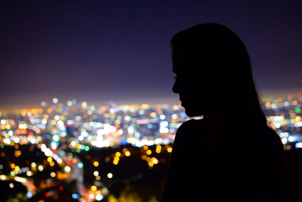 Woman in silhouette overlooking city