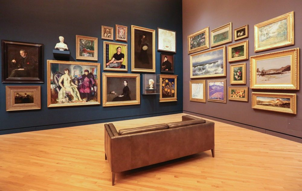 Sofa in front of framed paintings at art museum