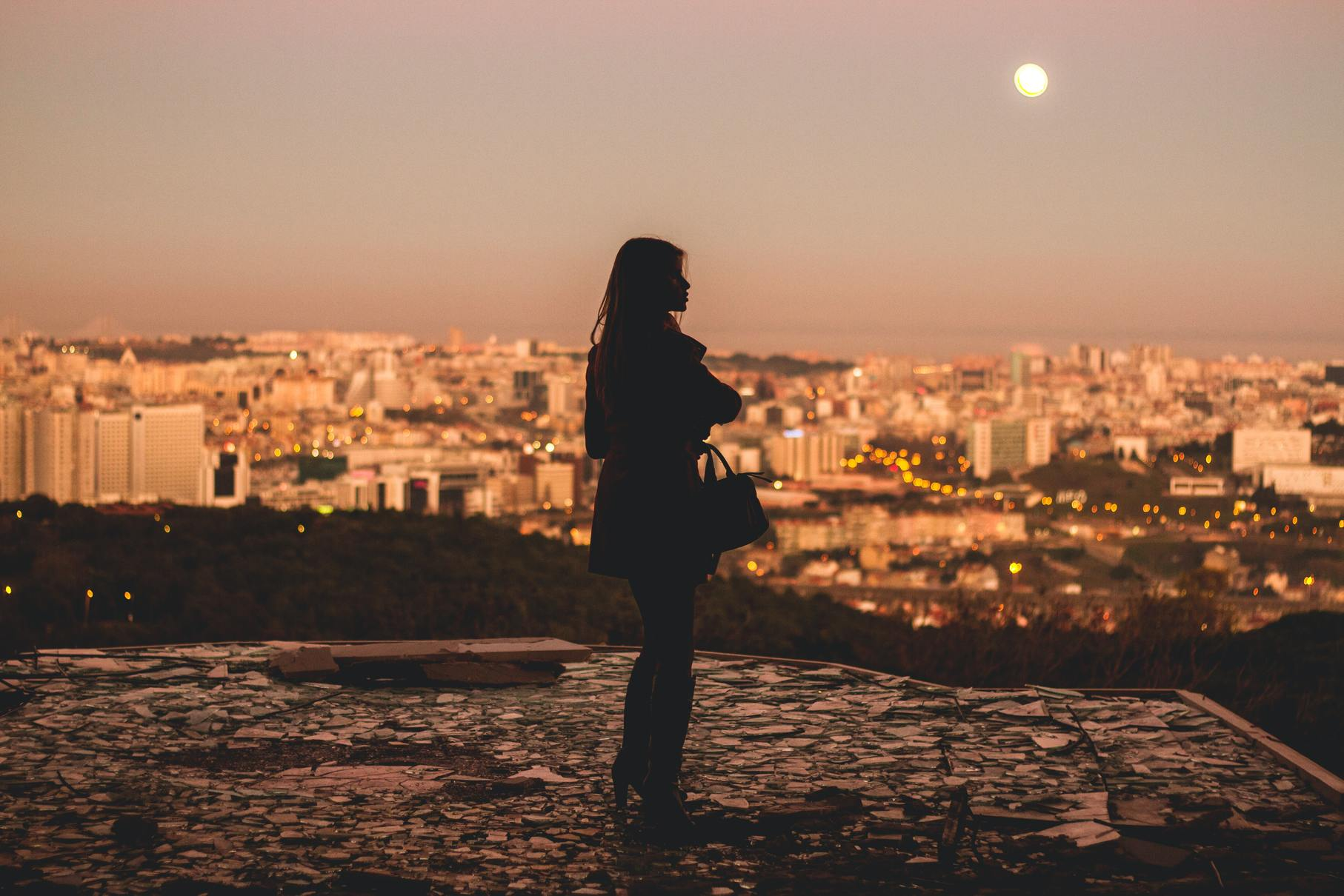 woman in silhouette standing before a city