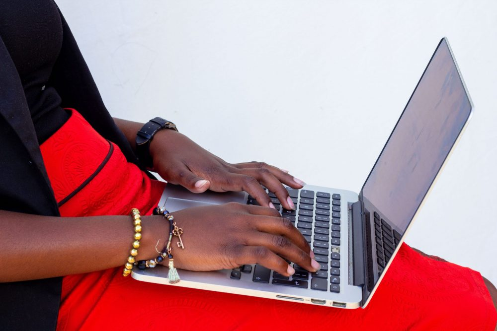 Black woman in bright red skirt typing on a laptop