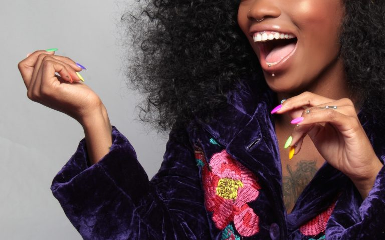 Black woman in colorful dress with colorful nails