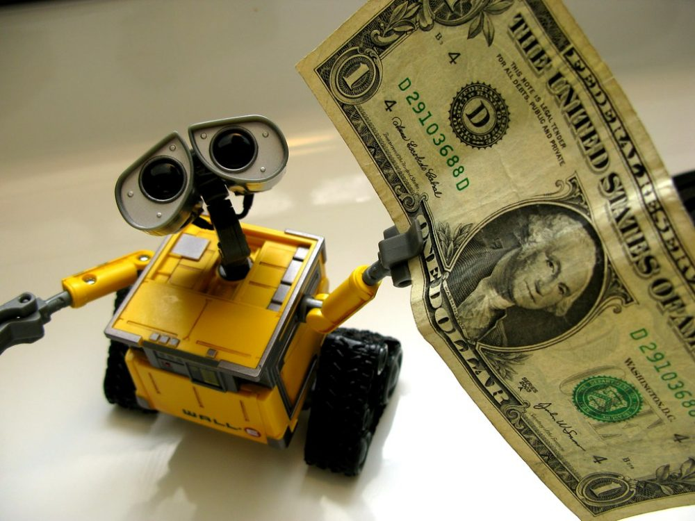 Toy robot holding a dollar bill