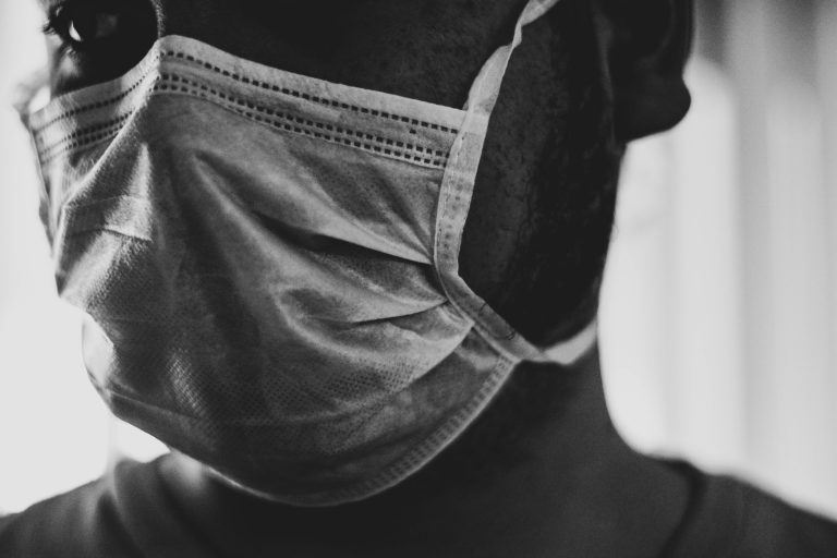 Black and white photo of man in surgical mask