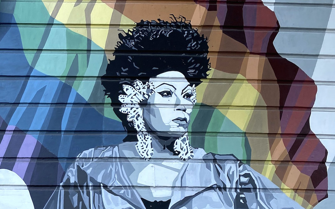Mural showing Black woman standing in front of rainbow flag