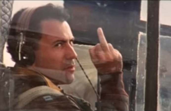 Yossarian sitting in an airplane ready to take off, giving the finger to the camera