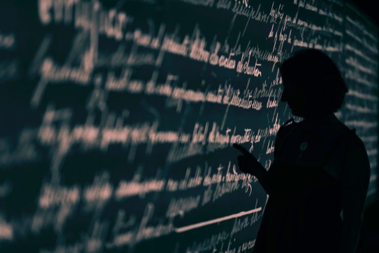 Silhouette of a person looking at words on a blackboard