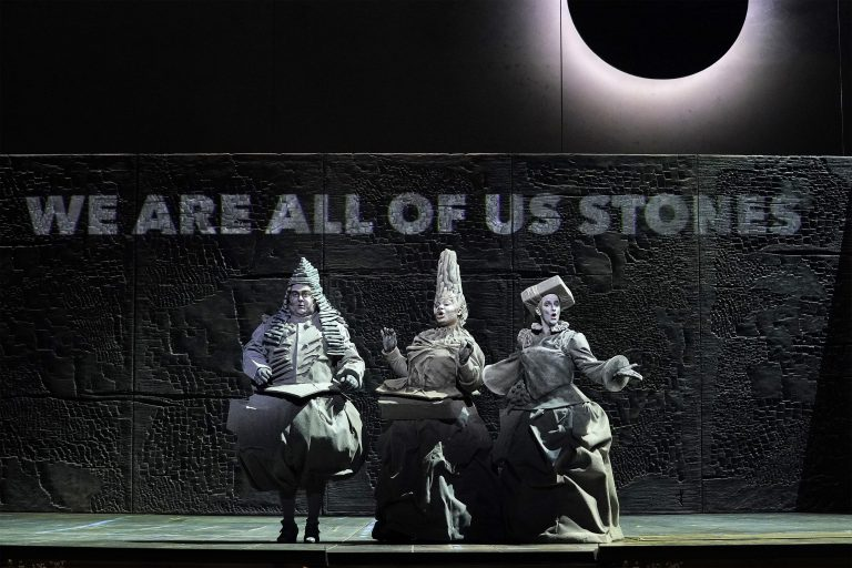 """Three opera singers dressed in ornate grey outfits, playing stones in Matthew Aucoin's opera """"Eurydice"""""""