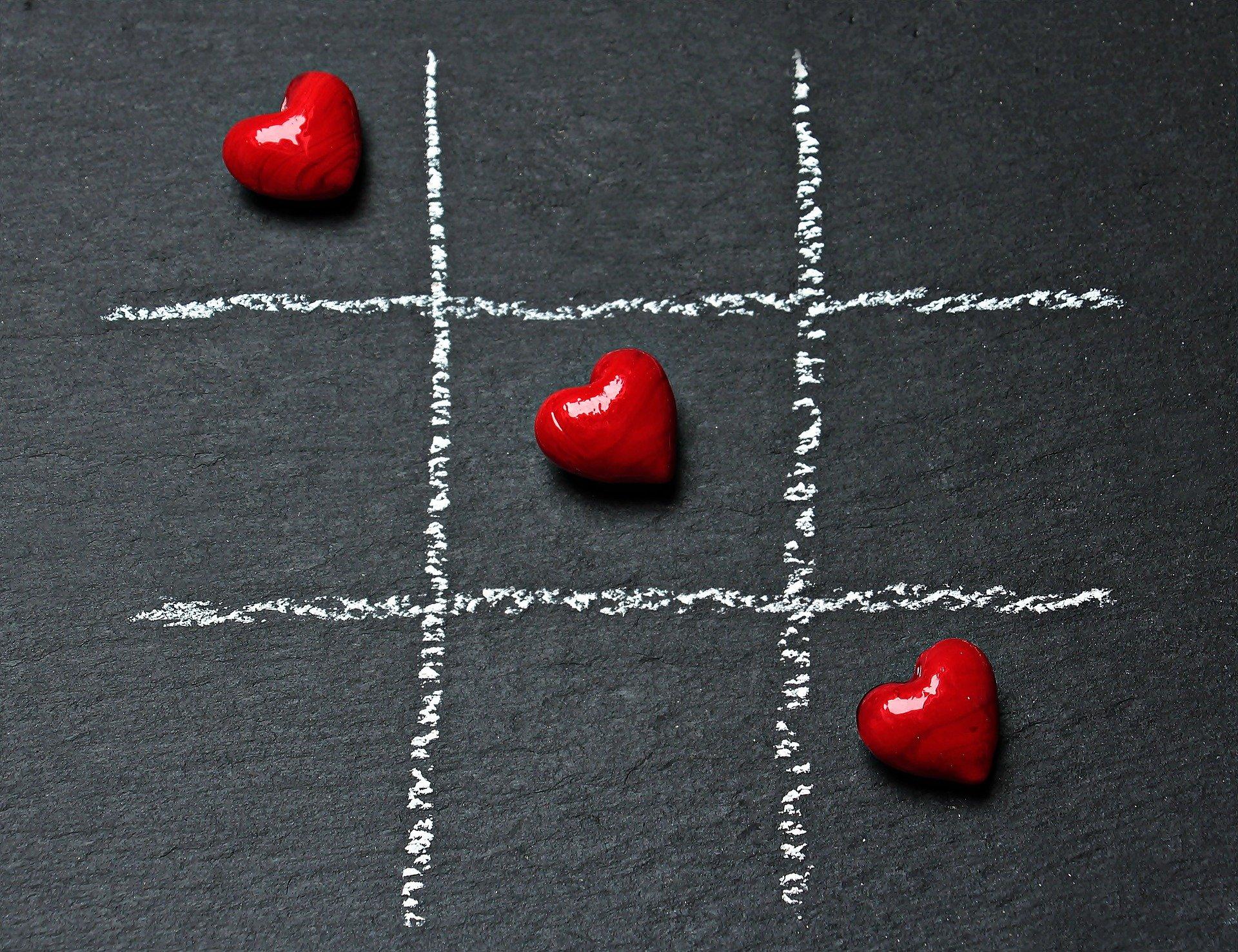 Chalk tic tac toe board with three diagonal hearts