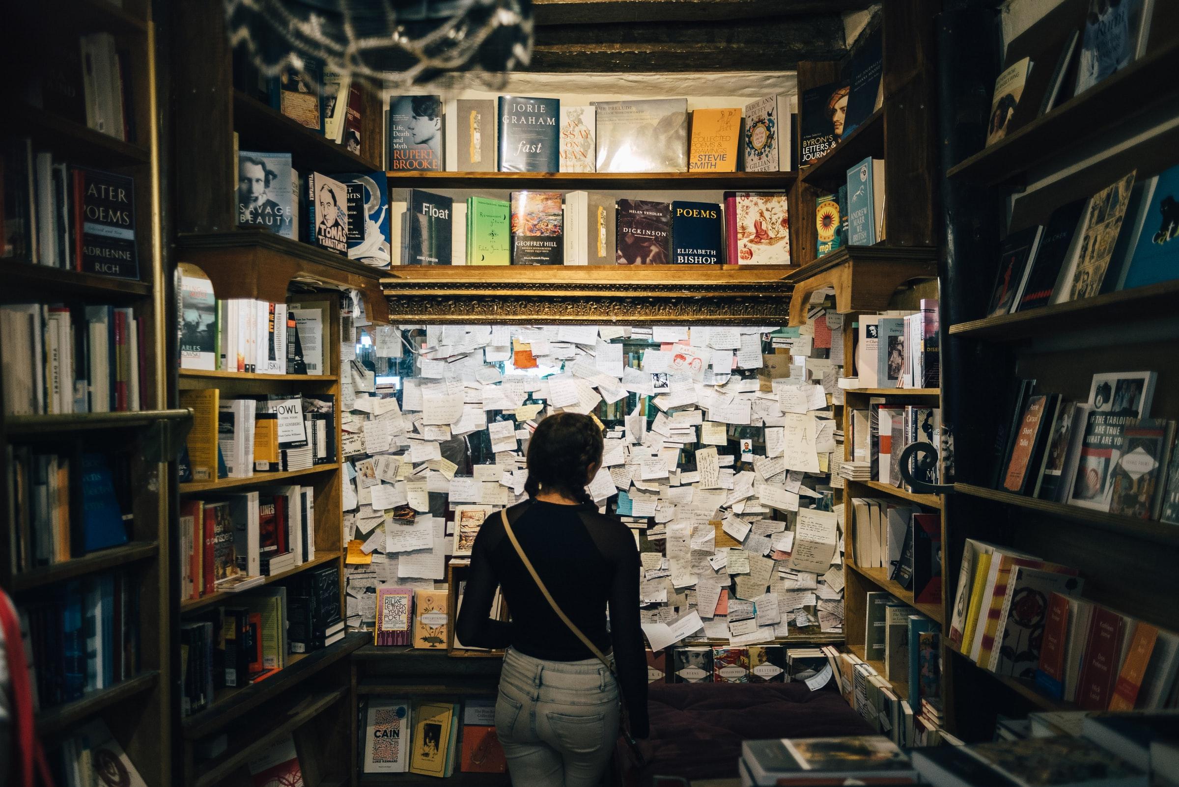 Woman looking at bulletin board in bookstore