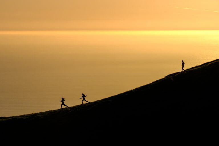 Three people running down a hill