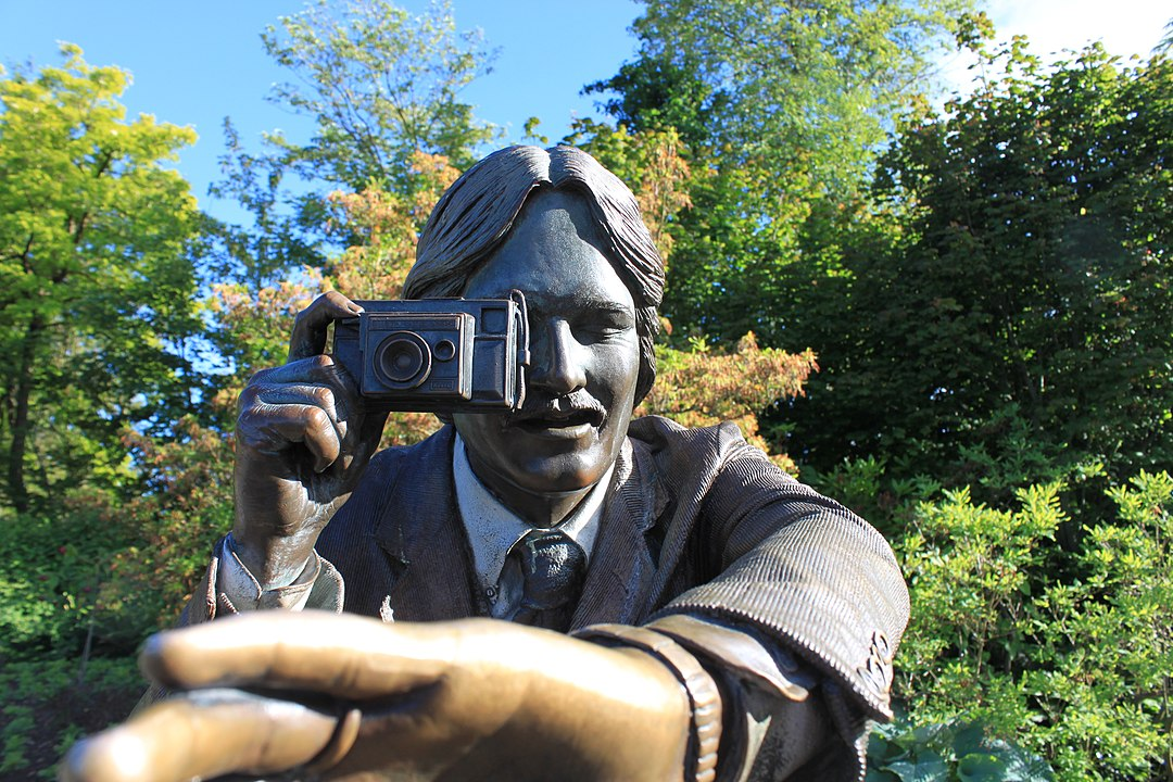 Bronze sculpture of a man taking a photo of the viewer