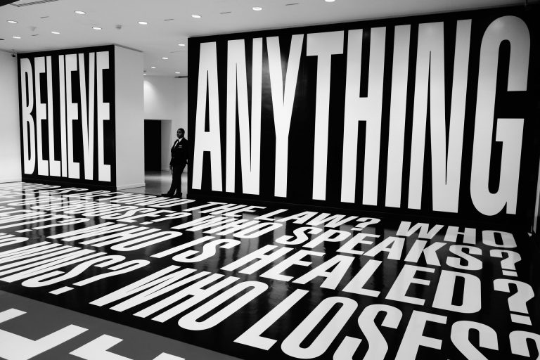 "Barbara Kruger installation including the words ""Believe Anything"" at full wall size"
