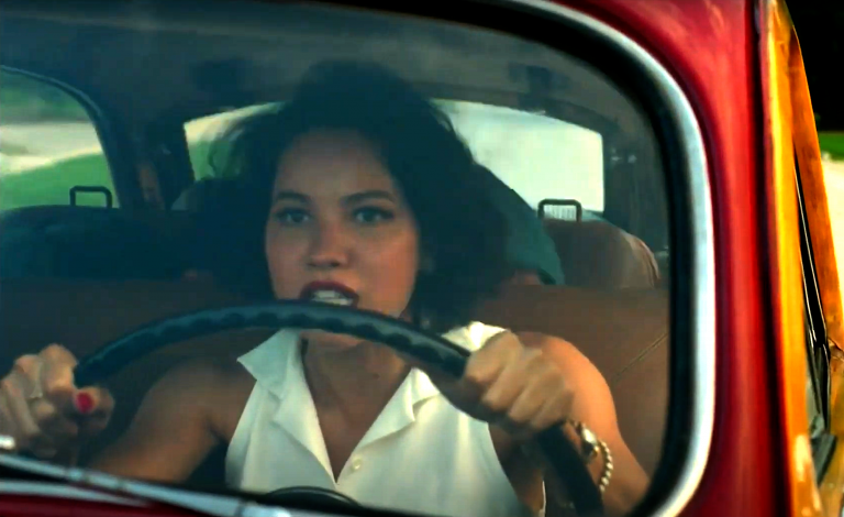 Jurnee Smollett looking very focused and tense, driving an old-fashioned car