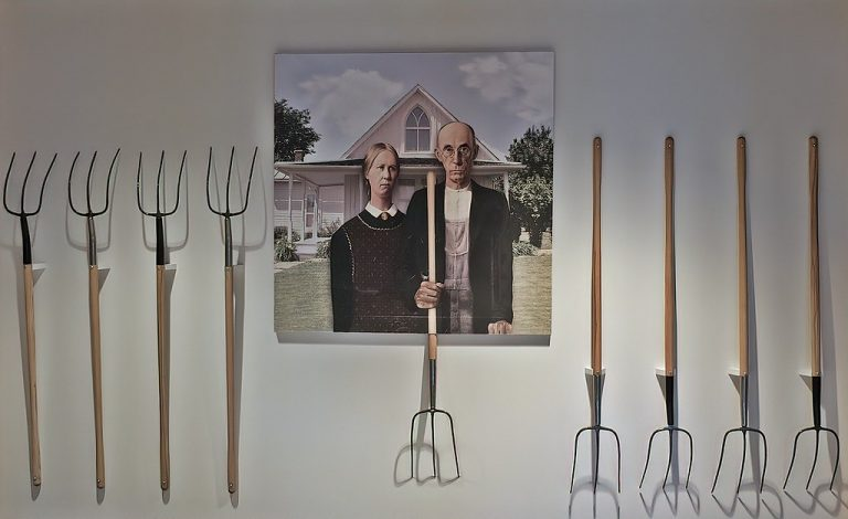A poster of American Gothic surrounded by real pitchforks