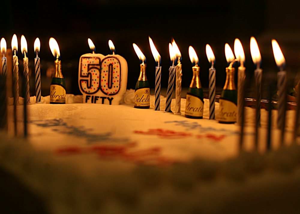 "Cake with a candle reading ""50"""