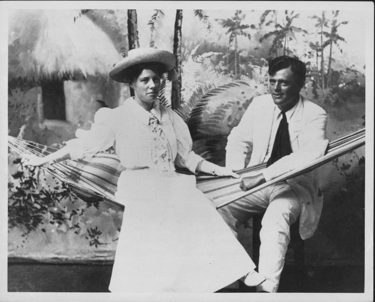 Black and white photo of a woman in a white early-20th-century dress with a hat and tie, sitting in a hammock, accompanied by a man in a white suit